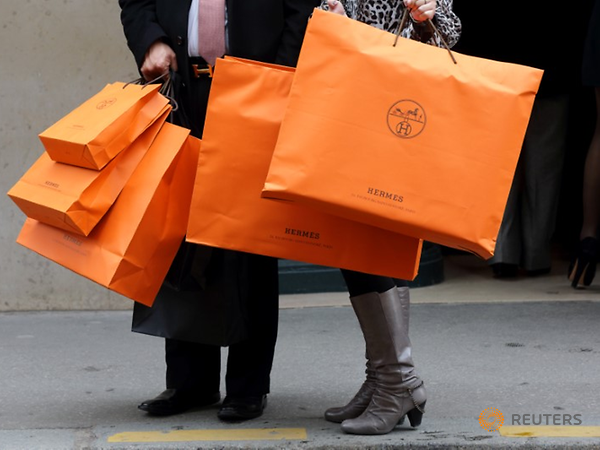 <p>A couple walk with Hermes shopping bags as they leave a Hermes store in Paris, France, March 21, 2013. REUTERS/Philippe Wojazer/File Photo</p>