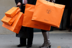 a-couple-walk-with-hermes-shopping-bags-as-they-leave-a-hermes-store-in-paris---3259512